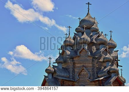 The Upper Part With The Domes Of The Old Wooden Orthodox Church Against The Blue Sky With White Clou