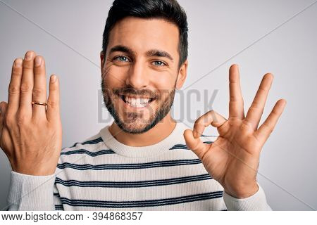 Handsome man with beard showing alliance ring marriage on finger over white background doing ok sign with fingers, excellent symbol