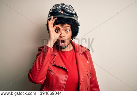 Young African American afro motorcyclist woman with curly hair wearing motorcycle helmet doing ok gesture shocked with surprised face, eye looking through fingers. Unbelieving expression.