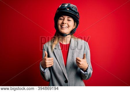 Young beautiful blonde motorcyclist woman wearing motorcycle helmet over red background success sign doing positive gesture with hand, thumbs up smiling and happy. Cheerful expression and winner