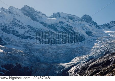 Rocky Mountains With Glacier And Snow. Peak Of Mountain And Ice Glacier In Dombay