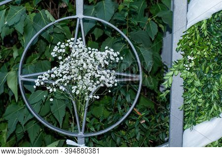 A Wrought Iron Ornament In The Railing At The Entrance Of A Church Decorated With White Flowers