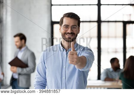 Satisfied Loyal Male Client Posing In Office Raising Thumb Up