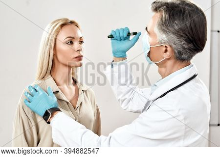 Visiting Ophthalmologist. Male Professional Doctor In Blue Sterile Gloves Examining Eyes Of Young Wo