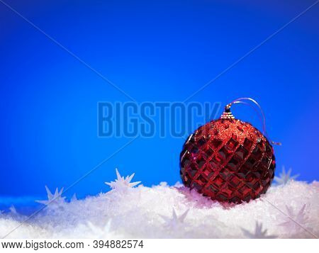 Red ball Christmas decoration on blue background with snow