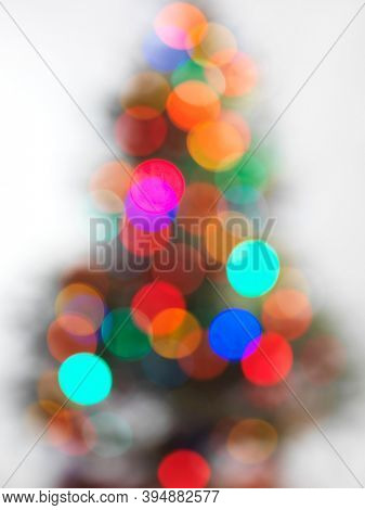 Out of focus decorated Christmas with colorful light tree on white background