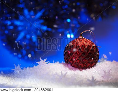 Sparkling Red ball Christmas decoration still life on blue background with snow