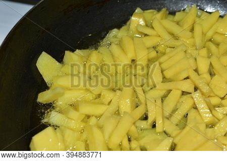 Frying Fresh Potatoes In A Frying Pan With Sunflower Oil