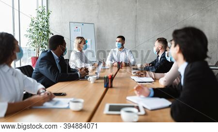 Business People In Face Masks Sitting At Desk During Corporate Meeting In Modern Office. Coworkers S