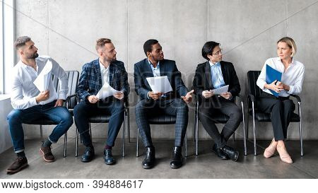 Sexism And Employment Discrimination. Diverse Men Staring At Woman Applicant Waiting For Job Intervi