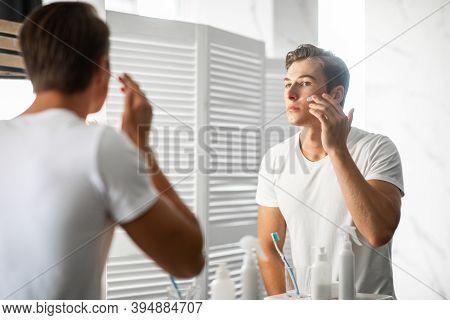 Male Facial Skincare Concept. Portrait Of Confident Handsome Man Applying Moisturizing Cream On Smoo