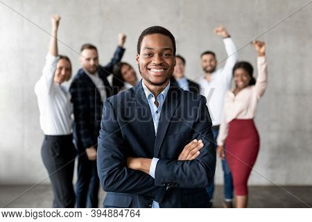Successful Black Businessman Standing In Front Of Joyful Business Team In Modern Office, Smiling To