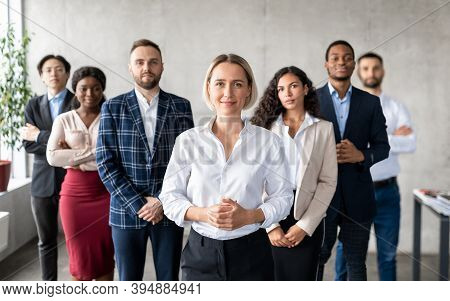 Successful Businesswoman Standing In Front Of Business Team Staff In Modern Office, Smiling To Camer