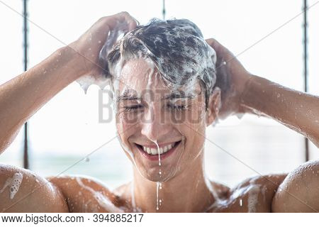Portrait Of Happy Smiling Young Guy Washing Head Caring For Hair Taking A Shower, Standing Under Fal