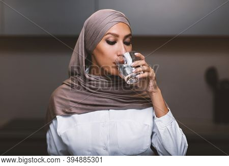 Stay Hydrated. Muslim Lady Drinking Water From Glass Sitting In Kitchen At Home, Wearing Hijab. Arab