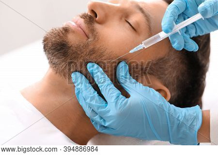 Closeup Of Bearded Man Getting Beauty Injection At Aesthetic Clinic. Plastic Surgeon Injecting Anti-