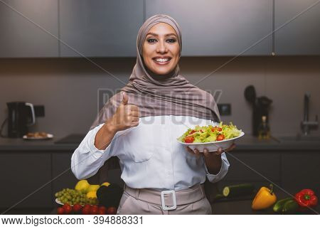 Arab Woman Holding Salad Bowl Gesturing Thumbs Up Approving Recipe Cooking In Kitchen Indoor, Posing