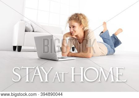 Young Woman Sitting On Floor With Laptop Computer, With Stay At Home Text Isolated On White Floor An