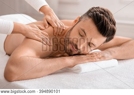 Closeup Of Relaxed Handsome Man Having Body Massage At Spa Salon. Middle Aged Bearded Man Attending