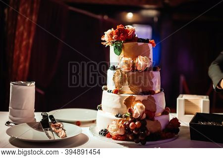 Four-tiered Wedding Cake On Table In Dark Hall.