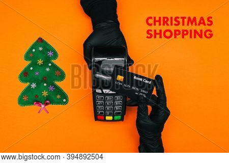 Christmas Shopping During A Pandemic. Payment Terminal, Hands In Black Disposable Gloves And A Chris