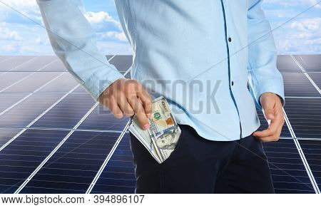 Man With Money And Installed Solar Panels On Background, Closeup. Economic Benefits Of Renewable Ene