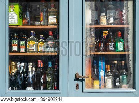Athens, Greece. November 10, 2020. Alcohol Spirits Bottles Display, Store Shelves Behind A Blue Glas