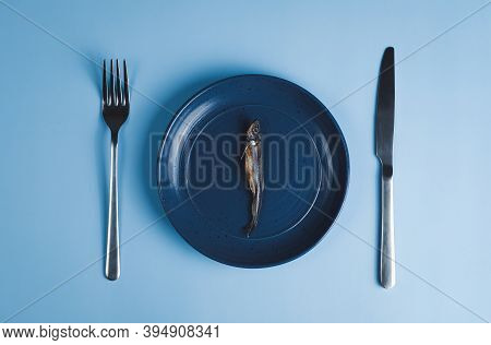 Dried Smelt Fish On Plate With Fork And Knife, High Angle View, Blue Background. Concept Of Diet Or