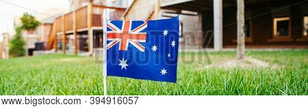 Australian Flag On Green Grass In Front Of House. Australia Day National Holiday Celebration. Nature