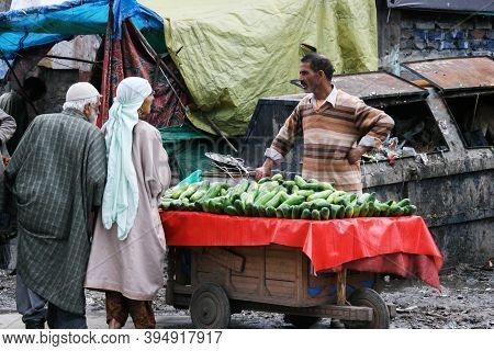 Kashmir, India - January 6, 2021 : Unidentified Man Selling Cucumber Vegetables And Talk With Custom
