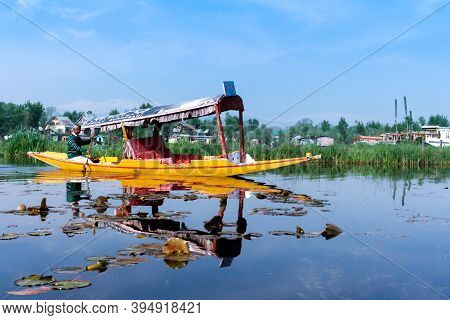 Kashmir, Jammu, India - January 7, 2021 : Man Rowing Traveling Boat For Tourist With His Reflection