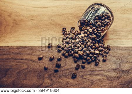 Coffee Beans In A Coffee Cup On Wooden Table. Top View Of Medium Roasted Coffee Beans For Coffee Dri