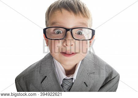 Portrait Of A Funny Child In Glasses And A Business Suit On A White Background. Smart Child In Suit