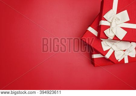 Red Gift Boxes On Red Background. Gift Boxes Tied With Gold Ribbon And Bows On Red Background. Top V