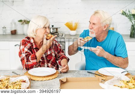 Senior Couple In Love Eating Pizza Together In The Kitchen At Home. Beautiful Elderly Woman And Grey