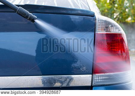 Washing A Dark Car With A Pressure Washer. The High-pressure Washer Nozzle Washes The Foam From The