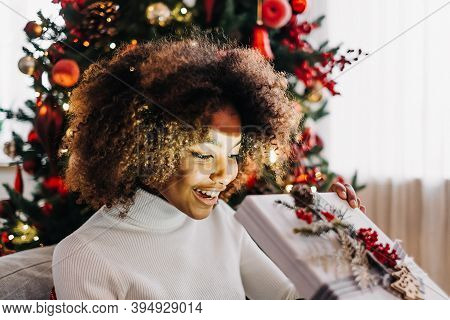 Young Woman With Dark Skin And Kinky Hair Opening Present Box And Smiling Widely Against Decorated C