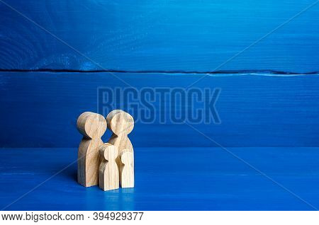 Family Figures Of Parents And Kids On A Blue Background. Family Values And Health. Adoption And Cust