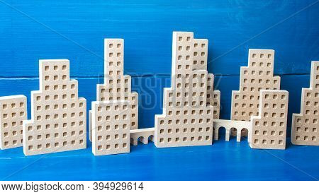 City Of Figures Of Buildings On A Blue Background. Concept For Real Estate, Urban Environment And Tr