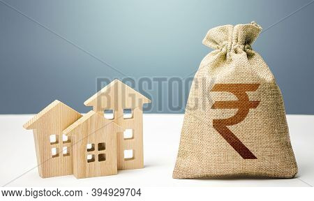 Indian Rupee Money Bag And Residential Buildings. Mortgage Loan. Costs Of Service And Maintaining Bu