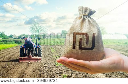 Hand Holds Out A Israeli Shekel And A Farmer On A Tractor Works The Farmer's Field. Financial Suppor
