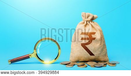 Indian Rupee Money Bag And Magnifying Glass. Revising The Budget To Save Money. Most Favorable Condi