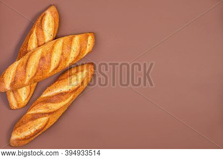 Three Freshly Baked Traditional Baguettes On A Brown Background With Copy Space. Top View, Flat Lay.