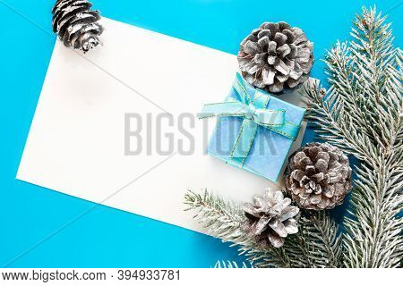 An Arrangement Of Christmas Frame With Fir Branches And A Gift Box. Blue Christmas Background With A