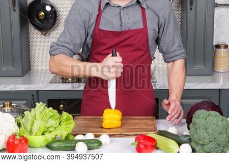 Ceramic Knife In Hand Cut Yellow Pepper Vegetable On Wooden Board In Kitchen. Vegetarian, Diet, Heal