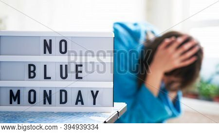 White Board With Text No Blue Monday On The Table, In The Background A Woman In Blue Clothes Depress