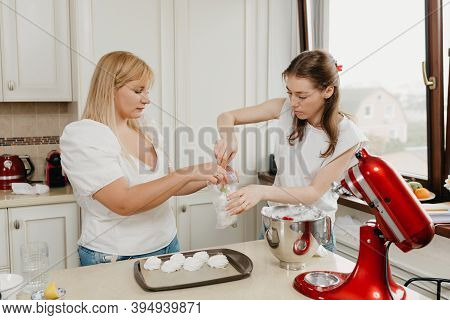 Two Young Women Are Putting The Meringue In A Transparent Plastic Bag In The Kitchen. Girls Are Prep