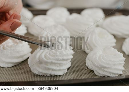 А Close Photo Of The Hands Of A Young Woman Who Is Creating With A Spoon A Form Of Meringues On A Tr