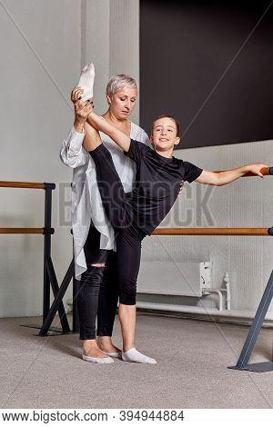 A Woman Teaches A Young Man Ballet. Lift Your Leg High Up, Flexibility Training.