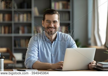 Office Employee Sitting At Desk Smiling Looking At Camera